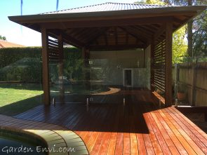 Spotted Gum Gazebo with multiple features including solid Spotted Gum Posts, two framed and sided walls, Spotted Gum screening, Cedar ceiling, exposed F27 Spotted Gum rafters, Colorbond Roof, elevated deck set to the height of the pool surround with Merbau decking fit to curve around the pool.